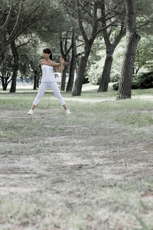 rehearse: Woman stretching in a park LANG_EVOIMAGES