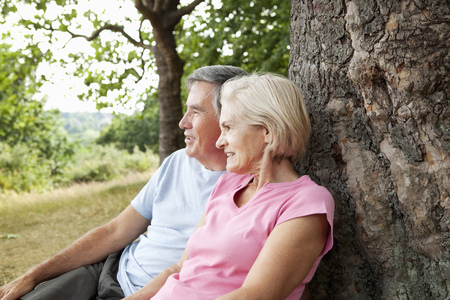 Mature couple sitting against tree LANG_EVOIMAGES