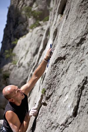 scaling: Rock climber securing himself LANG_EVOIMAGES