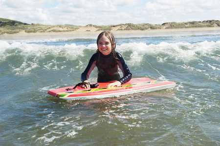 Young Girl in the sea with surf board LANG_EVOIMAGES