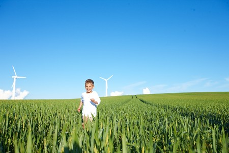 remoteness: Boy running on field with wind turbines