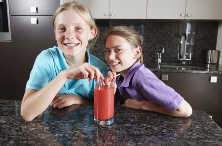 shared sharing: Girls drinking fruit juice with straws