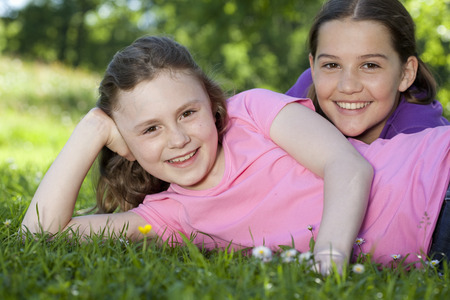 lays down: Two girls resting in meadow, happy