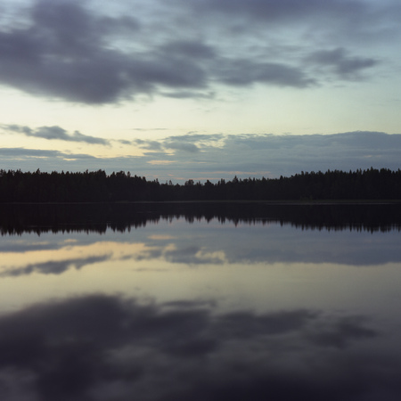motionless: Sky and trees reflected in lake at night