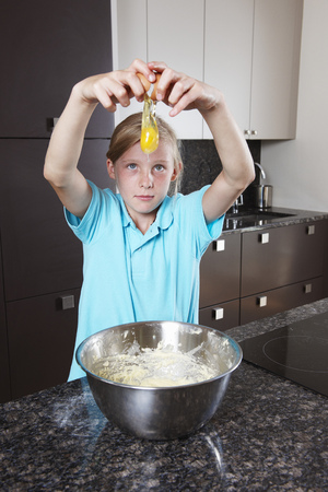 Girl breaking and egg over mixing bowl