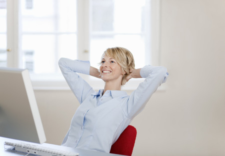 leans on hand: Young woman relaxing at desk