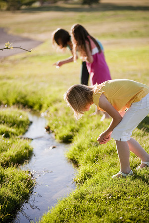 3 young girls looking in creek LANG_EVOIMAGES