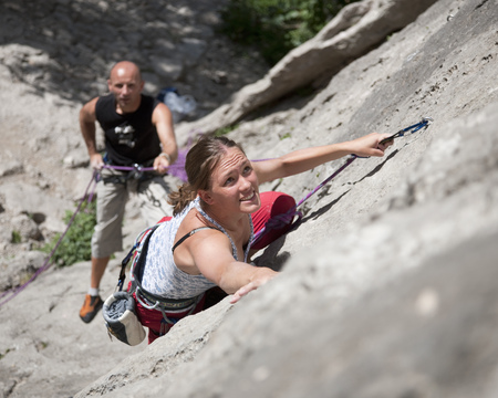 jeopardizing: Rock climber climbing rock face LANG_EVOIMAGES