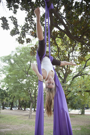 dangling: Young woman doing acrobatics in the tree