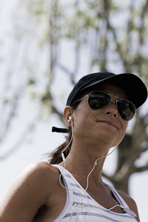 Woman smiling with sunglasses and cap