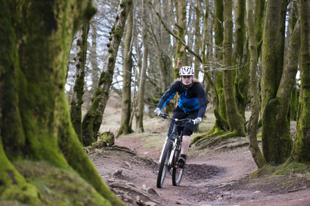 ciclos: Woman mountain biking in woods
