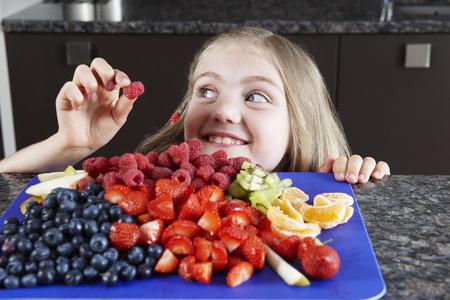 tempted: Girl choosing some fruit