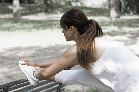 warming up: Woman stretching on a bench LANG_EVOIMAGES