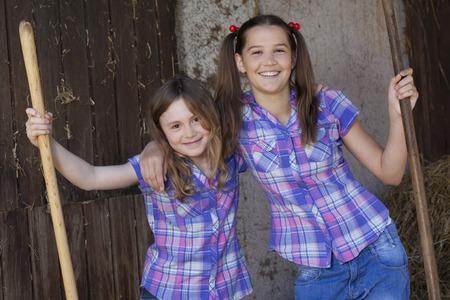 equivalents: Two girls resting on hayforks