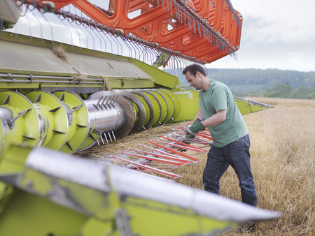 sustain: Farmer doing maintenance on harvester