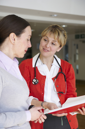 diagnoses: Female doctor with book talking to woman