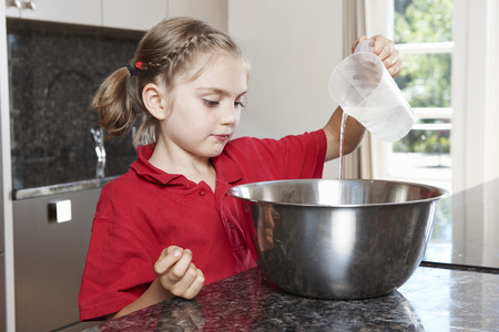 Girl pouring water in to mixing bowl