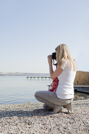 blue waters: Woman taking pictures at a sea