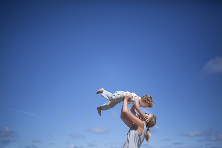 arms lifted up: Woman holding son LANG_EVOIMAGES