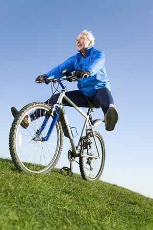 enthusiastically: Senior man riding mountain bike