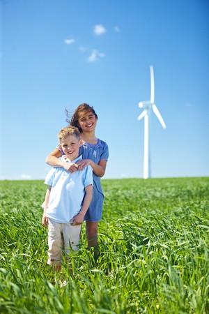 alternative living: Girl and boy at wind turbine LANG_EVOIMAGES