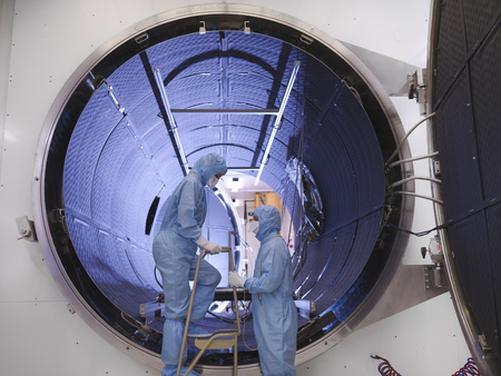 scaling ladder: Workers with satellite testing chamber