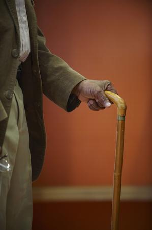 help section: Elderly mans hand on walking stick