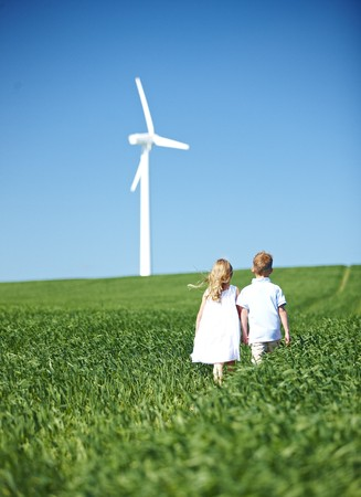 in twos: Boy and girl lookng at wind turbine