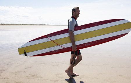 Male Surfer carrying board on beach LANG_EVOIMAGES