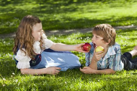 Girl feeding boy with apple