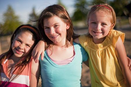 curare teneramente: 3 ragazze sorridenti che abbracciano LANG_EVOIMAGES