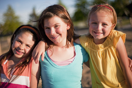 hearted: 3 smiling young girls hugging