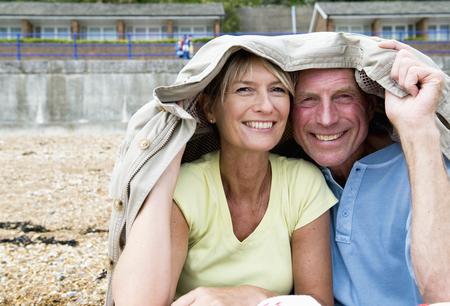 cuddled: Seniors shelter under coat on beach