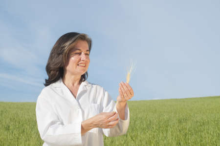 new age: Female scientist in field with seedling