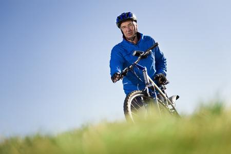 defended: Senior man pushing mountain bike