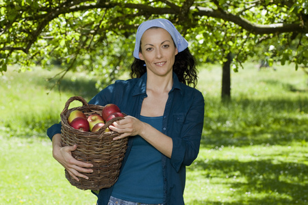 Woman with basket filled with apples