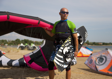 Kitesurfer holding kite and board LANG_EVOIMAGES