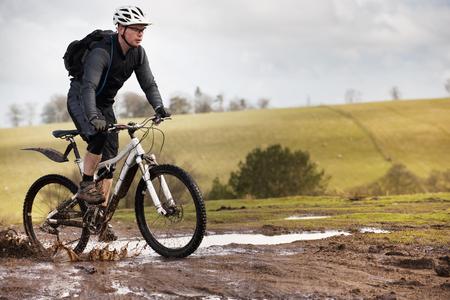 dirtied: Man riding mountain bike through mud