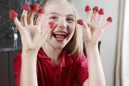 Girl with raspberries on fingers LANG_EVOIMAGES