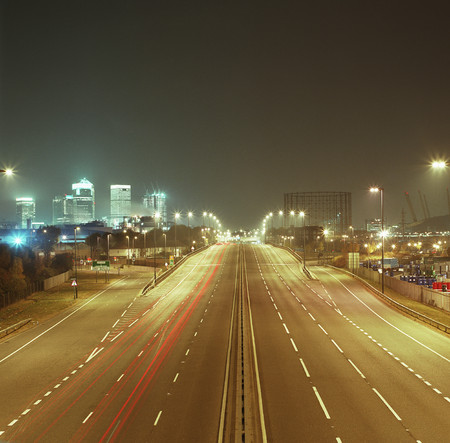 turnpike: Road leading towards cityscape at night