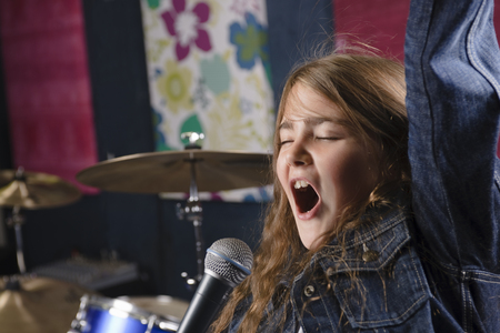 musically: Young girl singing in studio