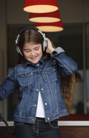 Young girl listening on headphones