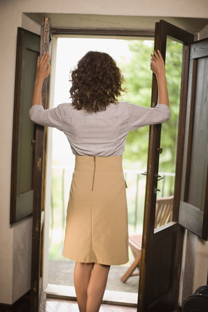 lodgings: Woman looking out of a door