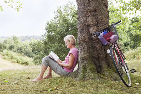 ceasing: Mature woman reading book in park