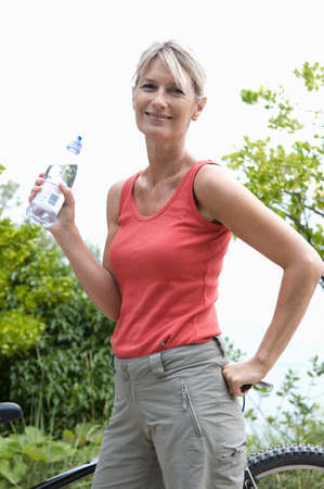 ceasing: Healthy senior takes drink after workout