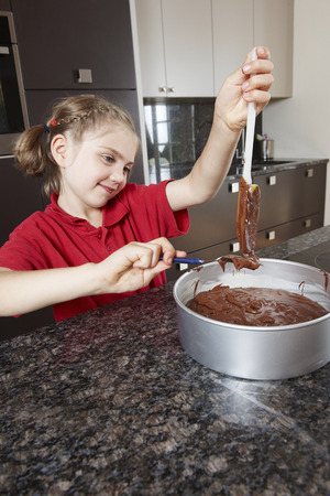 adds: Girl pouring cake mix into cake tin