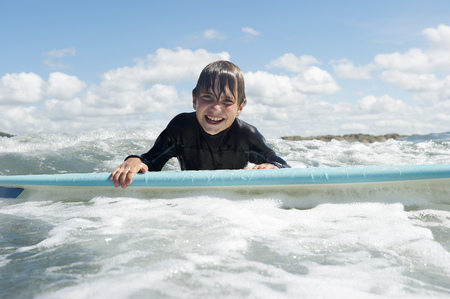 pelo castaño claro: Chico joven en la tabla de surf en el mar LANG_EVOIMAGES