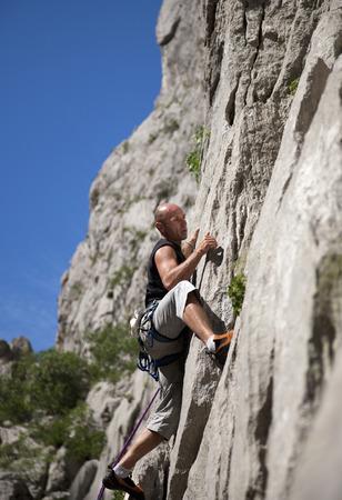Rock climber climbing rock face LANG_EVOIMAGES