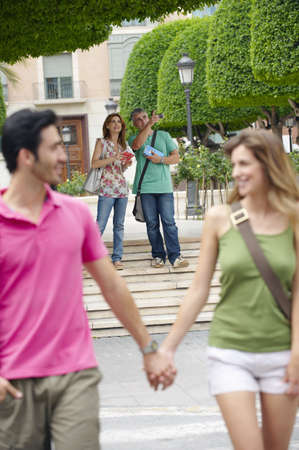 passions: Couple holding hands crossing street LANG_EVOIMAGES