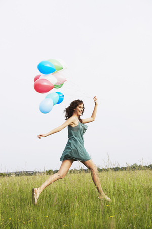 Woman with air balloons jumping